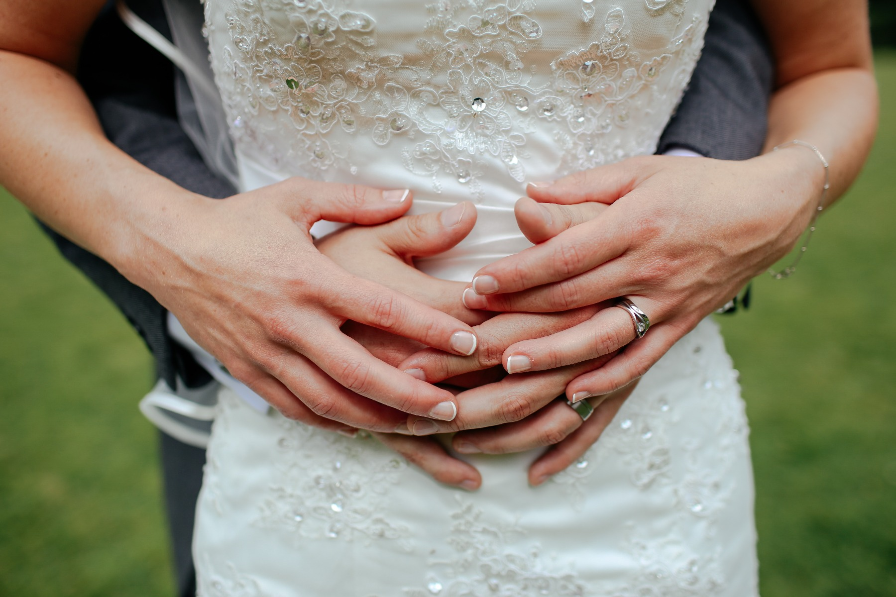Bride with her arms wrapped around her husband, showing off her beautiful ring.