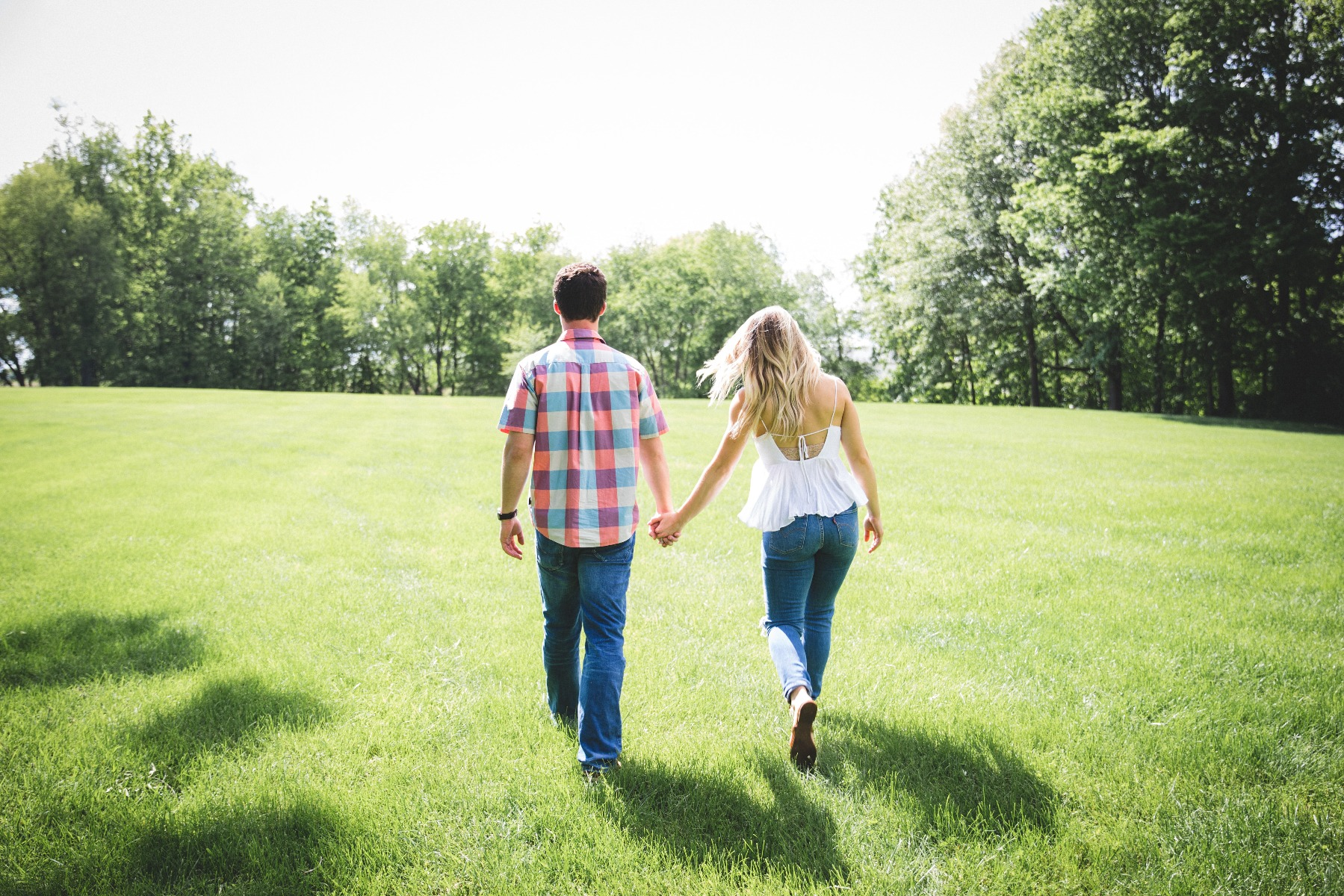 Man and woman standing side-by-side holding hands.