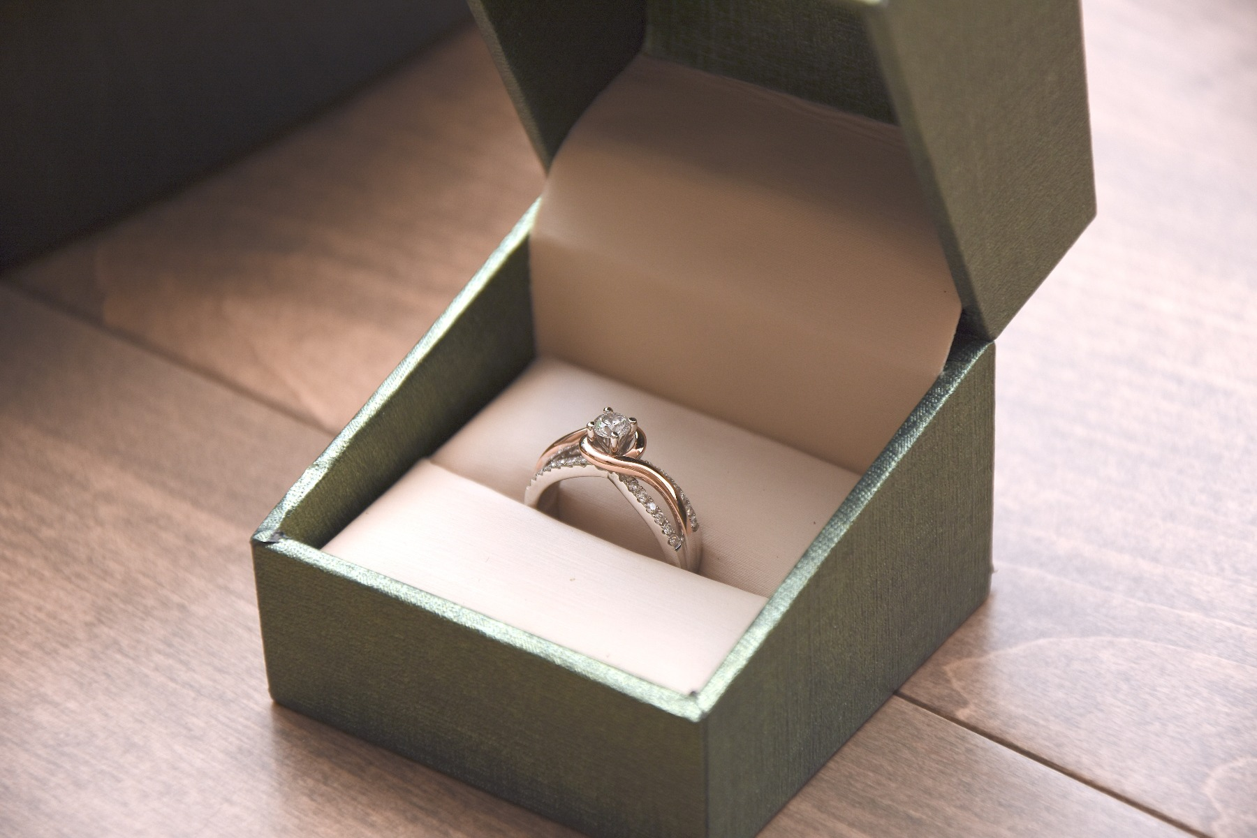 Beautiful engagement ring sitting on a wood table