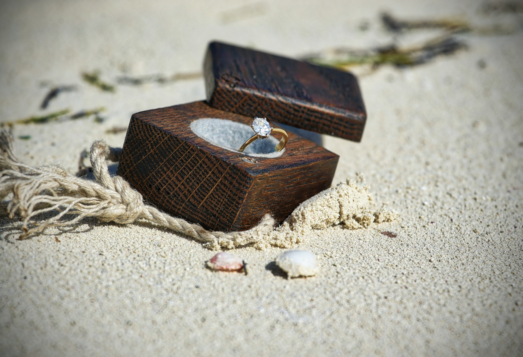 Engagement ring in an engagement box in the sand on a beach