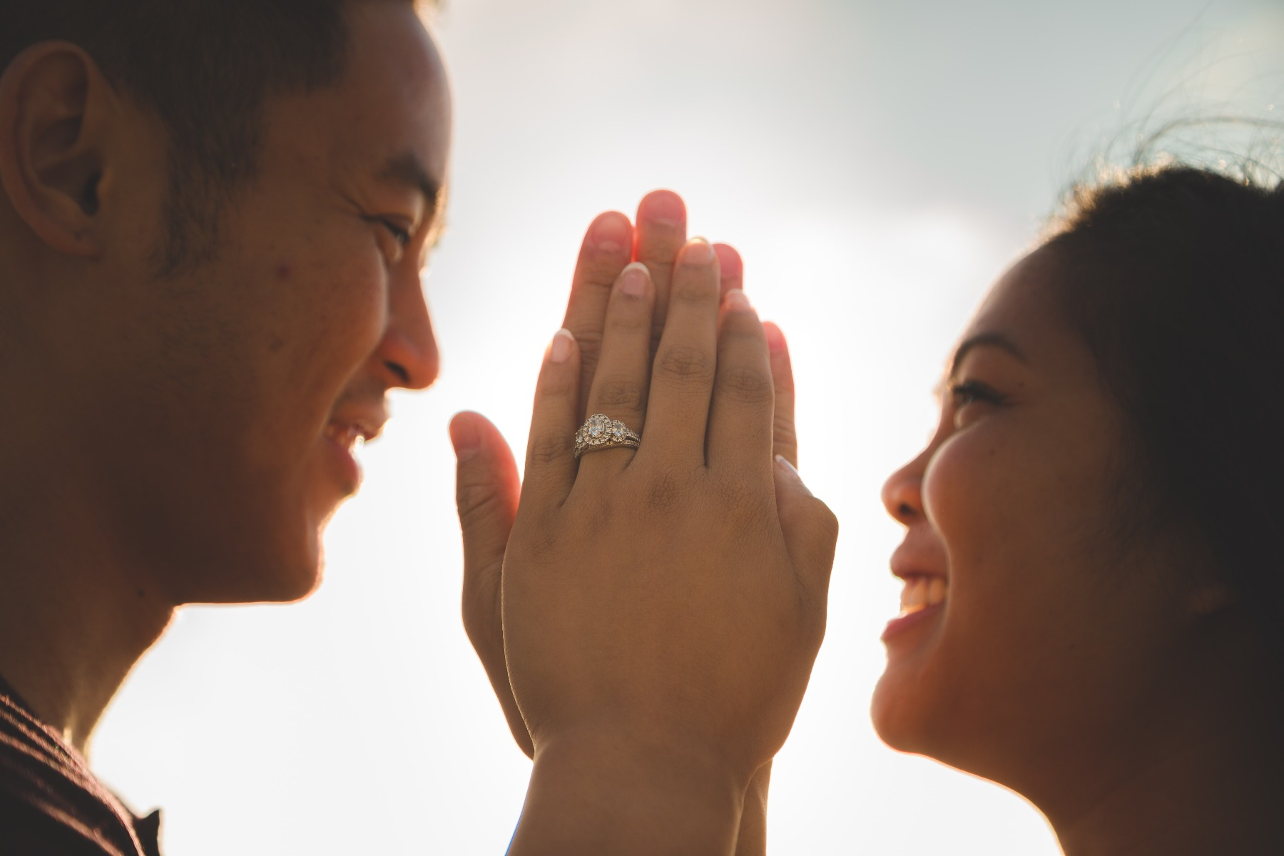 A man and a woman kissing each other while the woman holds her engagement ring up to the camera